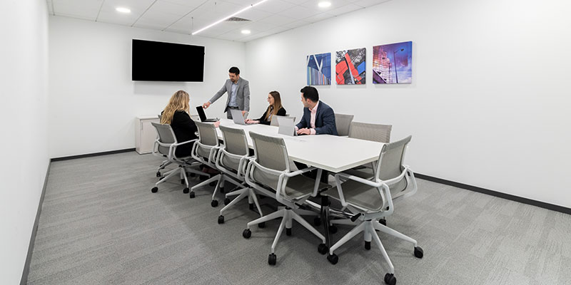 A man is stood presenting to two women and a man around a large meeting room table